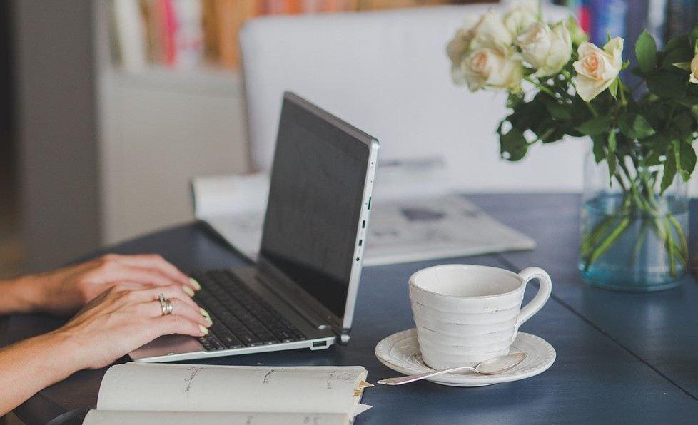 Schriftverkehr, Arbeit mit mobilem Computer, auf Bild: Tisch, Blumen, Stühle, Raum im Hintergrund