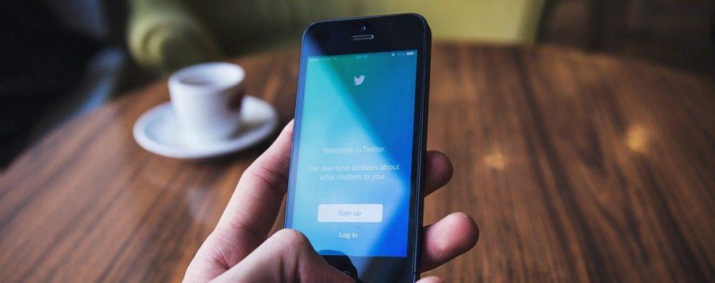 Twitter App auf Smartphone, Kaffeetasse auf Tisch im Hintergrund