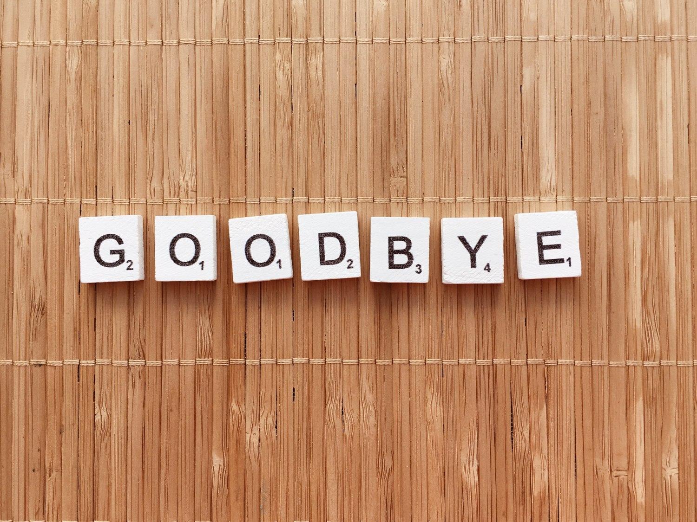 Goodbye, Schrift mit Scrabble Puzzleteilen und Holzbalken-Hintergrund