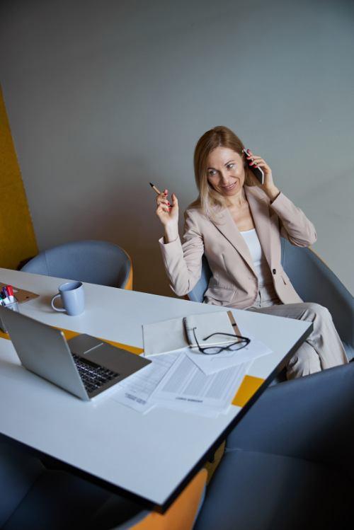 Fröhliche Geschäftsfrau in angenehmen Gespräch