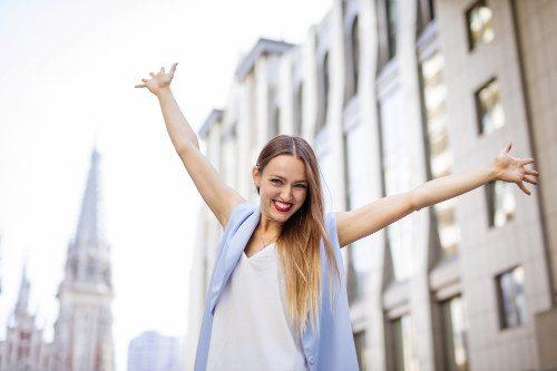 Junge Frau hebt ihre Arme vor Freude