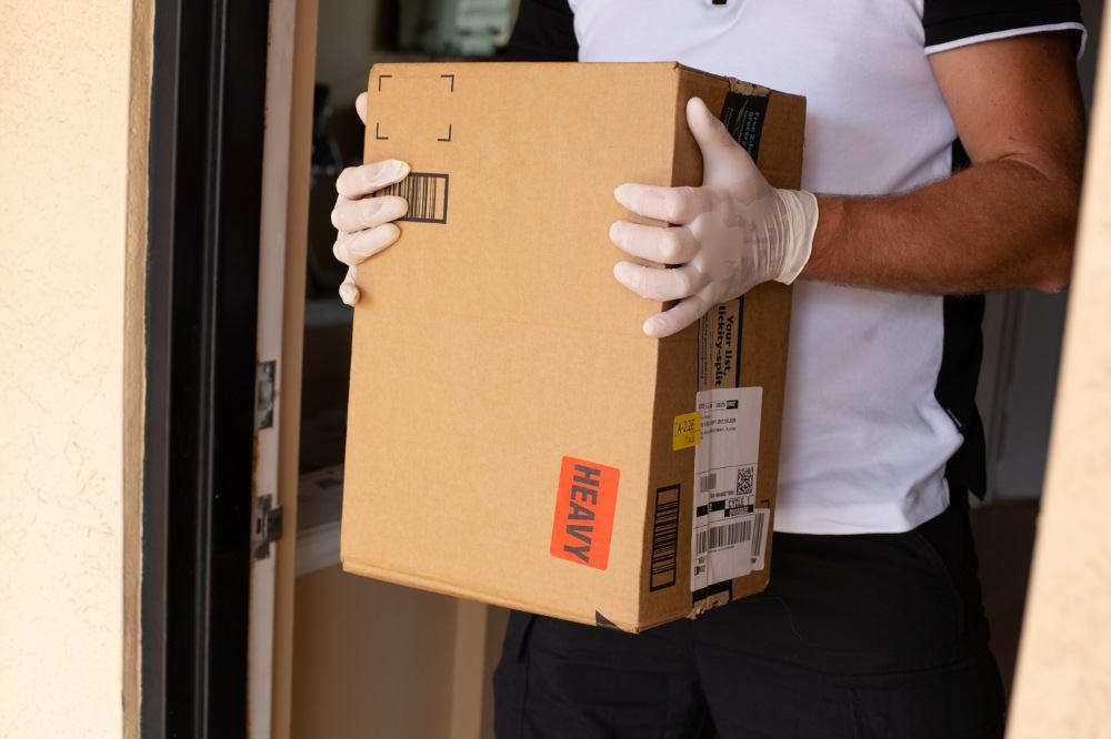 Mann hält Amazon Prime Paket an der Wohungstüre